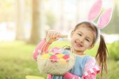 Cute little girl with basket of colorful eggs in park. Easter hunt concept poster