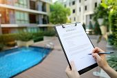Large Hand Portrait Of Subscribers Sign Contract On Background Of New Building With Swimming Pool. C poster