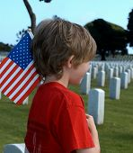 stock photo of inhumane  - Child with an American Flag in a Military Cemetery - JPG