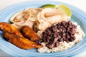 Traditional Cuban meal, of roast pork, black beans and rice, and sweet fried plantains.  Focus on th