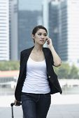 Business Woman Walking And Using A Cell Phone