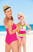Blue Sea, White Sand Paradise. Smiling Young Mother And Daughter In Colorful Swimwear On The Beach A poster