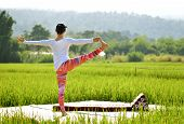 Soft Focus Image Of Woman Do Variation Of Utthita Hasta Padangusthasana Yoga Pose On Terrace In Gree poster