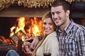 happy Young romantic couple and relaxing sofa in front of fireplace at winter season in home