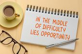 In the middle of difficulty lies opportunity - handwriting in a  sketchbook with a cup of coffee, up poster