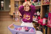 Adorable Little Girl Shopping For Toys. Cute Female In Toy Store. Happy Young Girl Selecting Toy poster