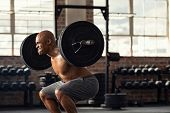 Determined african man lifting weight in gym. Muscular strong man taking efforts to lift weight barb poster