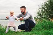 Dad Teaches Daughter To Walk, Park, Nature. Walk On The Grass. Father And Daughter. First Steps poster