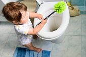 The Child Cleans The Toilet. Child Labour. Little Girl Cleans The Toilet. Toilet Brush. Grooming You poster