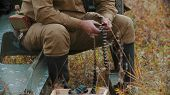 A Soldier Prepares The Ammunition For Charging In The Machine Gun - Inserts Bullets Into The Holes poster