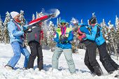 Young people having snowball fight in snow in winter background