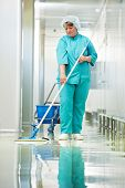 Adult cleaner maid woman with mop and uniform cleaning corridor pass floor of pharmacy industry fact