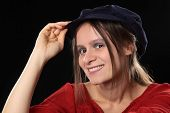 stock photo of newsboy  - Portrait of a young Caucasian woman smiling wearing a red shirt and a blue Gatsby cap  - JPG