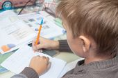 A Boy Writes English Words By Hand On Traditional White Paper In A Notebook. The Boy Writes His Firs poster
