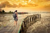 Tourist with backpack at Yeoh jetty at sunrise, Georgetown, Penang, Malaysia poster