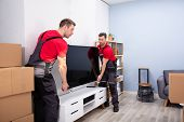 Two Male Professional Movers In Uniform Unloading Lcd Television In The Living Room poster