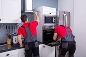 Two Male Technicians Fixing The Exhaust Hood And Oven In The Modular Kitchen poster
