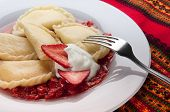 Varenyky or pierogy stuffed with cottage cheese, served with sour cream and strawberry sauce. A traditional Ukrainian or Polish dessert.