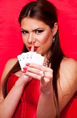 Attractive brunette holding four aces and showing shush sign with index finger on her lips, on the red background