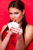 Morena atraente segurando quatro Ases e mostrando shush sinal com o dedo nos lábios, na r