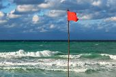 red flag on the beach during a storm