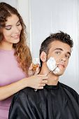stock photo of barber razor  - Portrait of mature man getting a shave from female barber at salon - JPG