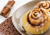 stock photo of cinnamon sticks  - yellow cinnamon rolls and natural cinnamon sticks - JPG