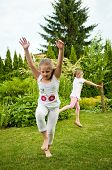 Children doing cartwheels in backyard