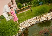 foto of fish pond  - Grandparent with her grandchild feeding fish in garden pond  - JPG