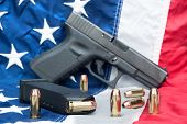 stock photo of cartridge  - A handgun with a full magazine and scattered bullets on an American flag - JPG