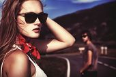 stock photo of country girl  - Couple of modern young people posing on a road over picturesque landscape - JPG
