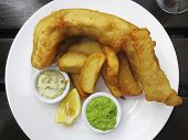 Fish and chips served with french fries, mushy peas and tartar sauce