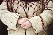 Close up of a child hands dressed in traditional Romanian wear