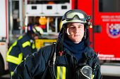 image of fire-breathing  - young fireman in uniform standing in front of firetruck - JPG