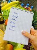 foto of local shop  - a woman holding a shopping list in a supermarket in the hand - JPG