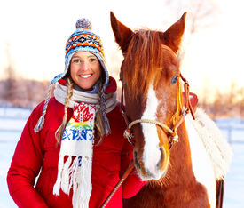 stock photo of winter sport  - Young happy smiling woman with horse - JPG