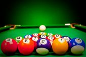 Fifteen billiard spheres lay on green cloth