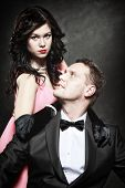stock photo of gangster  - Retro style attractive fashionable couple in love rich gangster with charming woman on black background - JPG