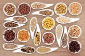 Large breakfast cereal sampler in porcelain dishes over papyrus background.