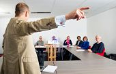 Male entrepreneur giving presentation to colleagues in conference room, focus on the pointing hand