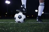 Close up of feet on top of soccer ball on the line