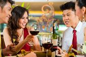 stock photo of chinese restaurant  - Two Asian Chinese Couples or friends or business people toasting during dinner or lunch in a elegant restaurant with red wine glasses - JPG