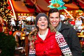 Man and woman or  a couple  or friends during advent season or holiday in front of a carousel or mer