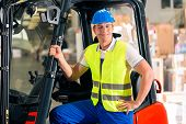 forklift driver in protective vest and forklift standing at warehouse of freight forwarding company,