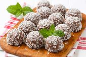 thirteen dark chocolate pralines breaded in a grated coconut, served on a wooden cutting board