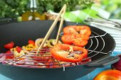 Vegetables in wok on wooden table on natural background