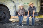 Two Young Boys Wearing Cowboy Hats Leaning Against an Antique Truck in a Rustic Country Setting.