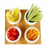 Bright fresh vegetables cut up slices in bowls isolated on white