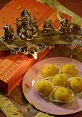 stock photo of laddu  - An box of Indian sweet and a traditional lamp - JPG
