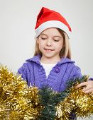 Smiling girl in Santa hat looking at tinsels at home during Christmas